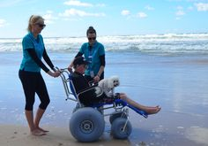 Tony Lambert was the first Gold Coast Health palliative care patient to use a beach wheelchair when occupational therapists Olivia Palac and Julie-Ann Hendry (supplied photo).