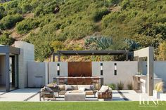 Jensen chose a sofa and chairs from Janus et Cie to face a built-in fire pit on the expansive terrace, which landscape architect Dirk J. Gaudet accented with channels of river rocks. A long custom dining table and bar-height chairs are by James de Wulf.