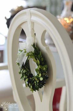 The dining table shouldn't be the only place in your dining room that gets some Christmas decor love! Tie a mini boxwood wreath onto the back of each chair for an unexpected touch.
