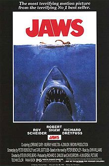 """Movie poster shows a woman in the ocean swimming to the right. Below her is a large shark, and only its head and open mouth with teeth can be seen. Within the image is the film's title and above it in a surrounding black background is the phrase """"The terrifying motion picture from the terrifying No. 1 best seller."""" The bottom of the image details the starring actors and lists credits and the MPAA rating."""