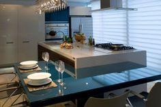cozinha com ilha central, acoplada a mesa de jantar azul