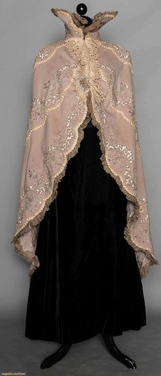 BEADED EVENING MANTLE, LATE 1880s Dove grey wool flannel, trimmed w/ cut-work, grey silk cord, cut steel beads, silver sequins, pale taupe silk ribbons, mantle cut-away from front to floor length in back, CBL 54""