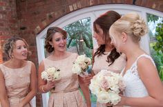 Bridesmaid's Bouquets of Quicksand and ivory Roses with antiqued gold pins to centres at Northbrook Park by Fiona Curry Flowers.