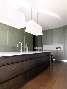 modern version of an Arts Crafts kitchen by Interni, contrast of clean lines of centre island, marble, lights with more traditional green Shaker style cabinetry