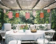 Burlap over a simple arbour made from small logs. Large bench behind a simple table draped with a long tablecloth.