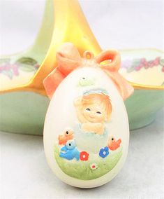 Ferrandiz Anri Egg Ornament, Baby Hatching From Egg, Made in Italy Egg measures 1 3/4 tall and 1 wide approximately. No props included.  A sweet egg ornament by Ferrandiz Anri. Resin egg hand painted pink bow wraps the egg and ties at the top. A happy little child looks as if she is hatching from the egg. With a chick sitting on her head.  Tie a cord on and hang from an ornament tree. Sit in a stand or put in a basket.  Marked Ferrandiz Anri Italy.  I have other eggs in my shop from this...