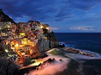 Locals gather at sunset near a boat ramp in Manarola, one of the coastal villages of Italy's Cinque Terre.