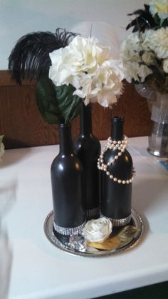 For Sale: Wine Bottle Arrangement, 6 available $15.00 each or all 6 for $75.00 Includes 3 wine bottles, 1 each black ostrich feather, white ostrich feather, and 1 hydrangea stem, silver charger, flower head and gold leaf, all other items sold separately.