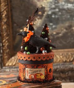 "Dress up your Halloween party table with a bit of vintage flair with this Halloween Party Crow Box. - Resin figurine on pressed paper box with bottle brush trees, glitter and tinsel accents. - 9"" x 5"""