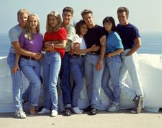 Jeans are in full demand, paired with colorful t-shirts for the 90210 cast photo. Steve Sanders (Ian Ziering), Kelly Taylor (Jennie Garth), Donna Martin (Tori Spelling), David Silver (Brian Austin Green), Andrea Zuckerman (Gabrielle Carteris), Brandon Walsh (Jason Priestley), Brenda Walsh (Shannen Doherty) and Dylan McKay (Luke Perry).