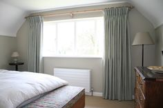 Hamada Stripe- Opal pinch pleat curtains in bedroom on a pale wooden pole. Opal is a soft eggshell green, white and natural striped linen. Here it gives a light airy look and  works well with floral fabrics.