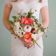 Coral charm peonies, pale pink garden roses, white anemones with touches of berries make a statement.