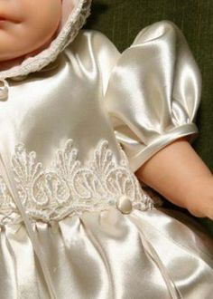 The wedding gowns lace adorns this lovely christening gown.