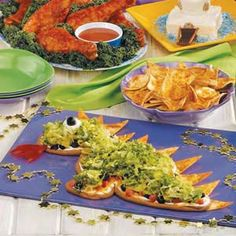 """Taco Dip Dragon Recipe.  Knights are sure to clamor for this mythical monster. Refried beans are spread into a dragon shape a & sprinkled with tempting toppings. Tortilla chip """"scales"""" line its back while red pepper """"flames"""" blaze from its mouth."""