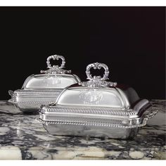 A Pair of George IV silver entree dishes and covers, Paul Storr, London, 1821 rectangular with incurved corners, the dishes with molded gadroon rims and handles cast as shells, engraved with contemporary hand crests, the conforming high dome covers with gadroon band and foliate ring finials, engraved with arms within foliate mantle, fully marked and numbered, bases stamped STORR & MORTIMER NEW BOND STREET length over handles 13in.