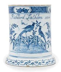 AN ENGLISH DELFT BLUE AND WHITE DATED MUG  1744, PROBABLY BRISTOL OR LIVERPOOL  Inscribed Richard Latham 1744 above stylised birds on a zig-zag fence issuing flowers below a diaper-pattern rim, supported on a domed foot  6½ in. (16.5 cm.) high