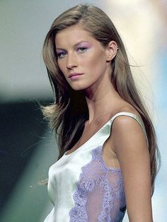 Gisele Bundchen, 1999: On the runway for the spring/summer 2000 Valentino runway show in Paris with soft waves, purple eyeshadow and mint green eyeliner | allure.com