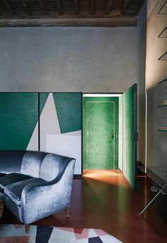 This meeting room has a secret door that, when closed, appears to be part of the armoire. The velvet-covered sofas throughout the house echo the lush seating common to the Prada stores. (Photo: Simon Watson)