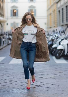 FLORENCE, ITALY - JANUARY 11: German fashion blogger and model Alexandra Lapp is wearing retro vibe Gucci printed cotton T-shirt, featuring a throwback Gucci logo, this piece features distressed detailing around the neckline, slim fit Wedgie Icon Fit Jeans from Levi's, suede /buckskin leather trench coat from Oui, Dionysus GG Supreme Medium Gucci shoulder bag, Le Specs sunglasses, red pumps from Gianvito Rossi on January 11, 2017 in Florence, Italy. (Photo by Christian Vierig/Getty Images)…