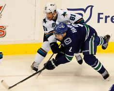 San Jose Sharks forward Tyler Kennedy + Vancouver Canucks defenseman Dan Hamhuis battle for the puck in the first period (Oct. 10, 2013).