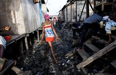 A woman walks to back to her room after bathing in what remains of Badia East, an informal settlement in Lagos, Nigeria on February 27, 2014. One year earlier, residents woke to construction equipment demolishing their community on order from Lagos State Government. Most only had time to get their children to safety, losing all businesses and belongings. Many took refuge with family and friends in the remaining portion of the settlement. Thousands are still displaced one year later. Image…