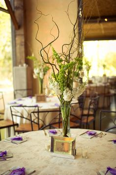 Cool Dining Table Decoration Of Twig Centerpieces Ideas : Charming Dining Room Design For Wedding Party With Tall Branches Decoration Plus Green Flowers On Glass Vase Combine With Round Table And Beige Table Sheet Also Rustic Iron Chairs