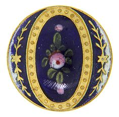 "At the center of this antique button is an emaux-peints floral design. The brass button measures 7/8"" in diameter."