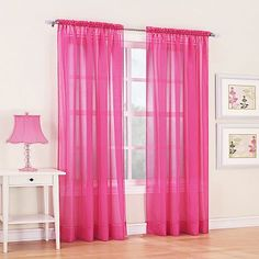 Pink sheer curtains hung up high to make the room look bigger