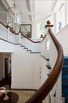 entryway with white walls, fabulous moulding | dark blue stair runner | lantern | classic and stunning