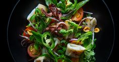 Spicy Squid Salad: a squid salad with cherry tomatoes, purslane, roasted peanuts, Thai basil and lime.