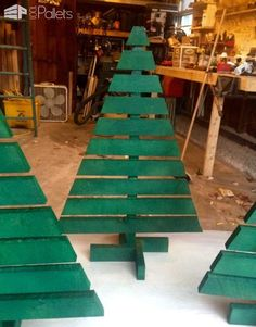 These four Christmas trees were made from salvaged soft maple pallets I got from work. I stripped the pallets with a pry bar and ripped the top slats in half. They were then glued and stapled to an upright bass made from the pallet runners.