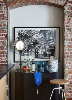 A cabinet doubles as a bar for entertaining. A young Hunter spotted the Brutalist, sunburst table mirror on Etsy.