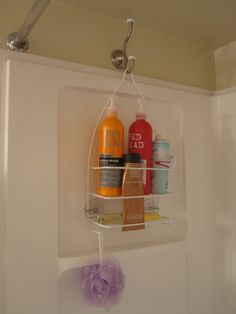 Hang a shower caddy on the opposite side of the shower with a coat hook so it doesn't interfere with the faucet