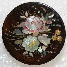 Date: ca. 1880 Culture: British. Horn button with inlaid mother-of-pearl florals which have been etched and hand colored. Tiny inlaid brass forget-me-nots, silver metal leaves and brass wire stems.