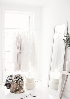 A thin white metal clothing rack is accented with neutral room accessories