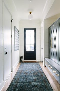 A black back door framed by white ship lap walls opens to a long mudroom featuring wood floors covered with a large blue overdyed runner positioned in front of a mudroom alcove boasting built in, navy blue closed paneled lockers with a matching bench sat atop navy blue drawers, both accented with brass pulls illuminated by a wall mounted glass globe pendant.