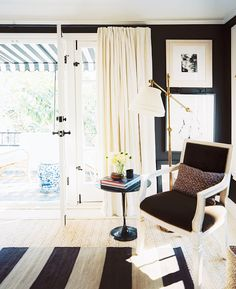 Elegant and feminine black and white living room with armchair and floor lamps.