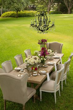 Outdoor Tablescape    Includes: Parker Dining Table, Eli Dining Chairs, Ethan Dining Chairs, and Kiera Chandelier.