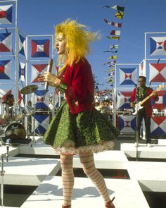 Cyndi Lauper live with yellow hair and stripy tights.