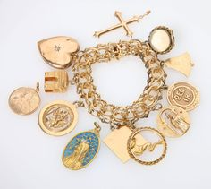 Lot# 1105 A 14K yellow gold charm bracelet.  suspending nine various gold and metal charms, and three unattached 14K yellow gold charms, 7.5'', 4 pcs, 105.3 gms, est: $2000/3000 *Price Realized: $2,700.00