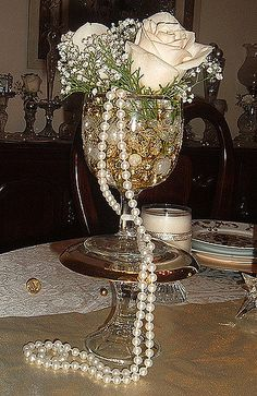 Vase created using a 1.00 glass candle stick with a gold rim saucer placed upside down on top. Then placed a mismatched goblet on top that is filled with pearls and gold beads.