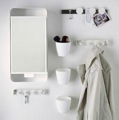 Área de parede pequena, com ganchos, armário espelhado, recipientes pequenos e quadro magnético para facas.