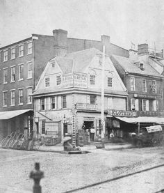 """c. 1854 photograph of the old """"London Coffee House,"""" at Market & Front Sts., Philadelphia, PA.  This building was built in 1702.  It sat at the very center of life in Philadelphia.  The market stalls running down the center of Market St ended at that same intersection, where the market's Head House was located in the middle of the street.  (By the time of this photo, the Head House was gone.)  Until the late 1740s, Pennsylvania's courts sat at the Head House.  The city's stocks, were right…"""