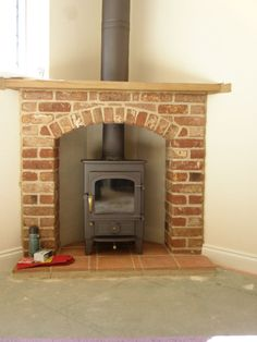 Charcoal Clearview Pioneer wood burning stove in corner fireplace with twinwall flue.