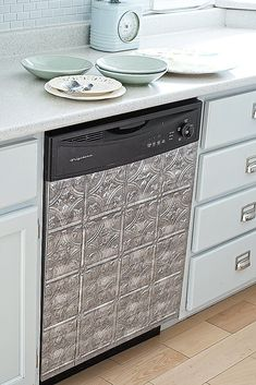 Faux-tin vinyl tiles cover a stainless steel dishwasher to add vintage detail to this blogger's kitchen.