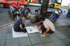 Мужики играют в шахматы рядом с королевским дворцом в Бангкоке