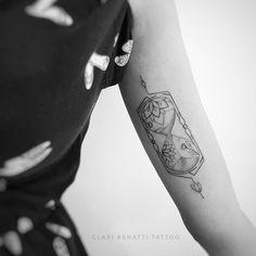 Tatuagem criada por Clari Benatti do Rio de Janeiro.  Ampulheta com flores em traços finos e delicados.