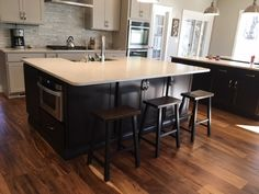 Counter height Saddle Stools with a Dark Walnut stained top and Black painted base.