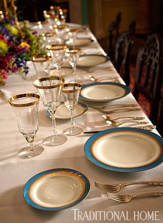Blue-rimmed dinnerware coordinates with the colors of the dining room walls. Gold-and-cyrstal goblets add elegance to the table. - Photo: Marco Ricca and Colleen Duffley