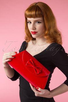Deze waanzinnige50s Stella Lacquer Bow Bag in Redis de nieuwste aanwinst in onze eigen ontworpen Boutique Collection en uiteraard exclusief verkrijgbaar bij TopVintage!Dit is toch gewoon de perfecte tas?! Een vintage look, felrode lak (daar hoeven we niet veel meer over te zeggen, L-O-V-E!), een super schattige strik, een afneembare riem en genoeg ruimte voor je telefoon, portemonnee, sleutels en make-up. Daarnaast is hijvolledig gevoerd met glanzend sateen met een zwa...